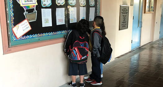 Two students looking at an i-Ready progress wall.