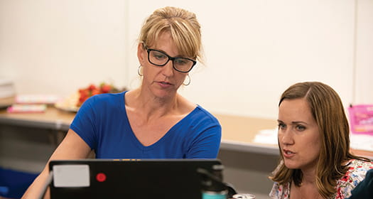 Two teachers in discussion together in front of laptop.