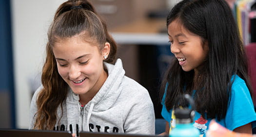 Two students smiling in class.