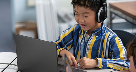 Student with headphones using laptop.