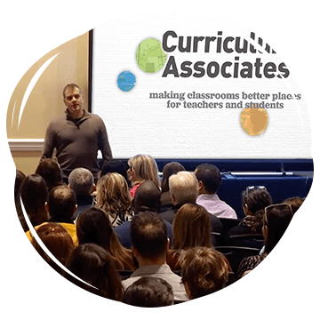 CEO Rob Waldron speaking to Curriculum Associates employees in front of projection with logo and slogan: making classrooms better places for teachers and students.