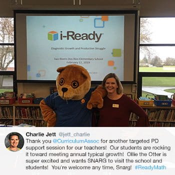 Teacher posing for a photo with the Ollie the Otter mascot in front of a projector screen showing the i-Ready logo.