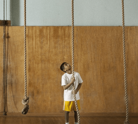 Young boy preparing to climb up rope.
