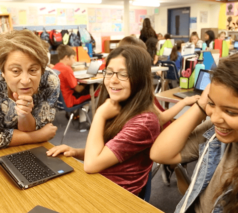 A teacher working with two students in i-Ready.